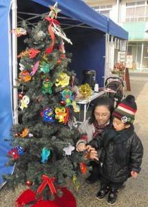 クリスマスツリーにうながっぱ短冊を付ける親子=多治見市本町で