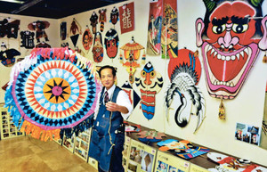 世界各地のたこのコレクションを見せる坂井田さん=津市西丸之内の津リージョンプラザで