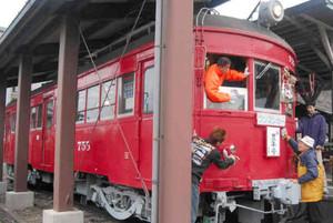 「赤い電車」の窓や車体をふく参加者=揖斐川町で