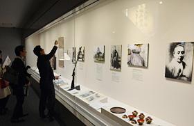 入館者に中央のスペンサー銃を説明する霊山歴史館の学芸員