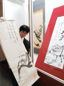 新たに見つかった眠そうな顔で描かれた百瀬正堂の達磨大師の絵(左)=松本市立博物館で
