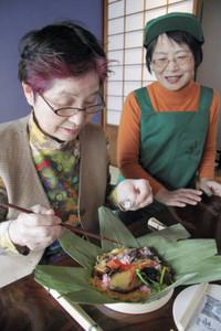 森田さん(右)のアドバイスを受けながら押しずしづくりに励む女性=金沢市東山で