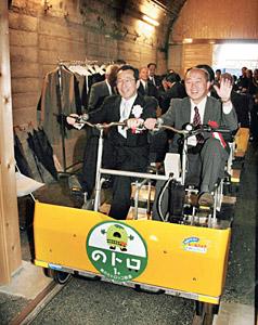 開通式で、のトロに試乗する徳力社長(左)ら=珠洲市宝立町で