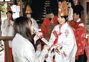 花換神事の抽選会で当たった参拝者に縁起物の弓矢を贈る福娘(右から2人目)=敦賀市金ケ崎町の金崎宮で