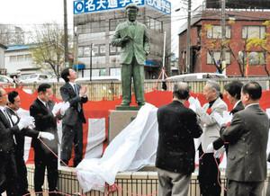 関係者らの手で除幕された江戸川乱歩の銅像=名張市の近鉄名張駅東口で