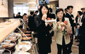 県産の食品を試食する嘉田由紀子知事(右)と越直美大津市長=名神高速道路大津SAで