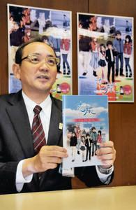 恋旅のポスターを背に特製カードブックを持ち「ぜひアニメを楽しみに、南砺に来て」と呼びかける田中市長=南砺市役所城端庁舎で
