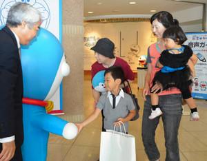 入場7万人目になり、ドラえもんの着ぐるみと握手する悠斗君ら滝脇さん家族=高岡市美術館で