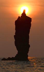 沈みゆく太陽が重なり、灯がともったように見える「ローソク島」