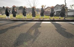 冬空の雲間に時折見せる日差しに照らされて、托鉢に回る雲水たち=永平寺町諏訪間で