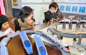 北陸新幹線の車両模型が走る様子を見つめる子どもたち=坂井市のエンゼルランドふくいで