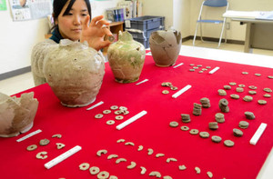 出土した古代貨幣と陶器。奥2点の陶器は緑色の上薬が塗られた水差し=栗東市内で