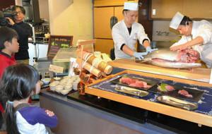 子どもたちの前で伊勢まぐろを解体する料理人=志摩市浜島町迫子の合歓の郷で
