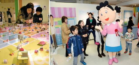 (右)子どもたちを出迎えるサザエさん (左)100円でミニチュアの分譲地に家を建てる被災地支援コーナー=いずれも金沢市の大和香林坊店で