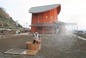塩田に海水をまく登谷良一さん=珠洲市清水町で