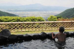 雄大な山々を望む露天風呂でくつろぐ協賛施設の温泉利用客=中野市間山で