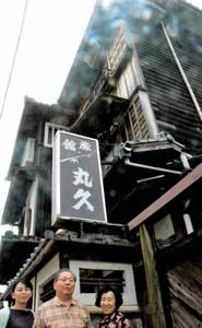 今秋にも取り壊されることになった丸久旅館の前に立つ(左から)柏野さん、井上豊さん、恵美子さん=常滑市鯉江本町で