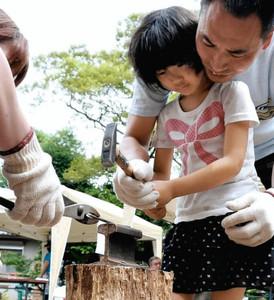 昨年のイベントで、五寸くぎをハンマーで打つ参加者=滋賀県長浜市鍛治屋町で(市提供)