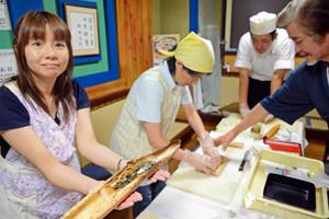 玉木健次さん(右)の指導で、焼きサバずしを仕上げる参加者ら=大野市の越前鯖の棒寿し本舗「日古里」で