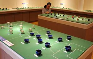 サッカー日本代表をイメージした青色のさかずきなどが並ぶ会場=多治見市市之倉町の市之倉さかづき美術館で