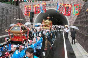 念願だった「神子トンネル」の開通を祝い、みこしを担ぎ通り初めする児童ら=若狭町神子で