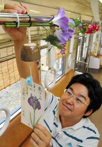 風鈴を車両に取り付ける社員=伊賀市の伊賀鉄道上野市駅で