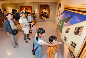 目の錯覚を利用した立体的な作品やアイデアあふれる絵画を楽しむ来場者=金沢市のめいてつ・エムザで