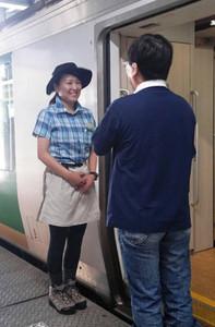 山ガール風の服装で乗客を迎える乗務員(左)=長野市のJR長野駅で(JR東日本長野支社提供)