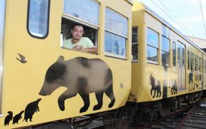 完成した切り絵ラッピング電車を紹介する早川鉄兵さん=彦根市内で