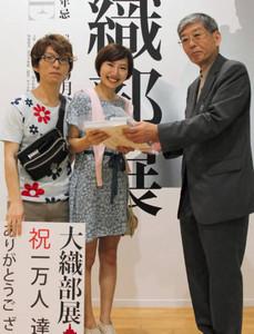 榎本徹館長(右)から図録を受け取る北崎麻耶さん(中)、市岡琢磨さん=多治見市の県現代陶芸美術館で