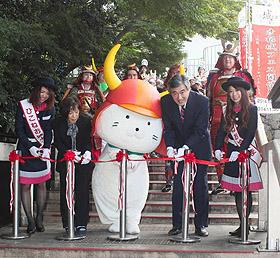 彦根城フェス開幕を祝いテープカットするひこにゃん(中央)と参加者たち=彦根市金亀町の開国記念館で