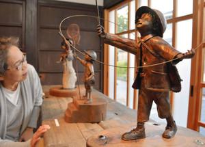 星を集める子どもなど、多彩な銅人形が並ぶ=東近江市五個荘川並町のカフェギャラリーハクモクレンで