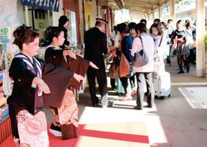 郷土芸能の和倉小唄で乗客を出迎える会員=七尾市のJR和倉温泉駅で
