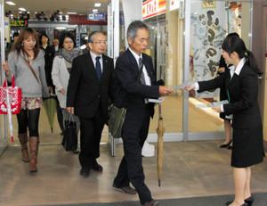 駅利用者にファンクラブの入会を呼び掛け募集チラシを配る社員=JR富山駅で