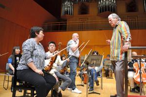 リハーサルで、楽団員と話す指揮者のサー・ネビル・マリナーさん=県立音楽堂で