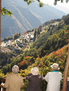 紅葉に囲まれた下栗の里の眺めを楽しむ人たち=飯田市で