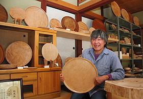 工房の展示室で自作の盆を手にする小椋昭二さん