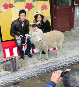 羊と記念撮影する親子連れ=長野市茶臼山動物園で