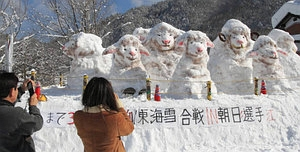 ヒツジの雪像を写真に収める観光客=高山市朝日町桑之島で