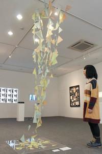絵をバラバラにした破片を高く躍動的につなぎ合わせた作品「完全な世界」=金沢市石引で