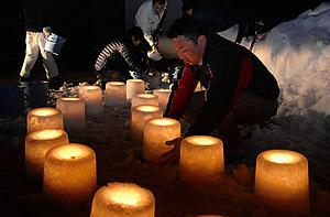 一つずつ手作りの雪灯籠を並べる稲武商工会青年部のメンバーら=豊田市武節町で