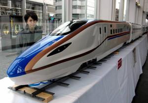 富山国際会議場1階に登場した北陸新幹線の新型車両W7系の模型。会議場の外から模型を眺める人も=富山市で