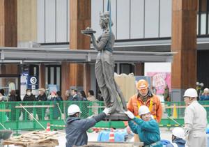 クレーンでつり上げられ、台座に戻された如是姫像=長野市のJR長野駅前で