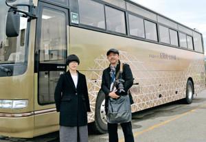 10日から運行する五箇山をイメージした世界遺産バスとデザインを担当した山本美智さん(左)と武山良三学部長=高岡市江尻で