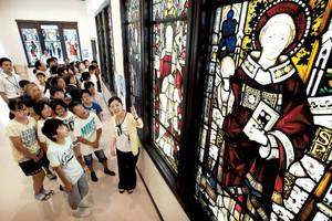 開館を前にした「掛川市ステンドグラス美術館」を訪れ、学芸員から説明を受ける市立第一小学校の児童ら=2日午後、掛川市掛川で