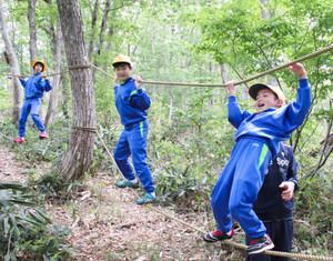 自然の中で綱渡りを楽しむ児童たち=南砺市利賀村百瀬川で