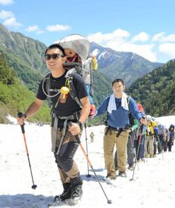 北アルプスをバックに雪渓を登る開山祭の参加者=大町市の針ノ木雪渓で