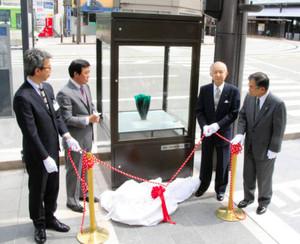 ガラス作品とともに、エキシビション・ショーケースをお披露目する森雅志市長(左から2人目)ら=富山市西町で