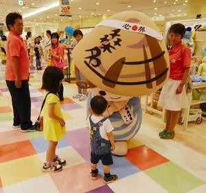 「必勝」と書いたハチマキを巻き、子どもと握手するゆめはまちゃん=名古屋市の名鉄百貨店で(桑名商工会議所提供)