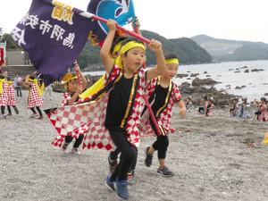 旗を振りながら元気良く踊る園児=鳥羽市安楽島町の市営安楽島海水浴場で